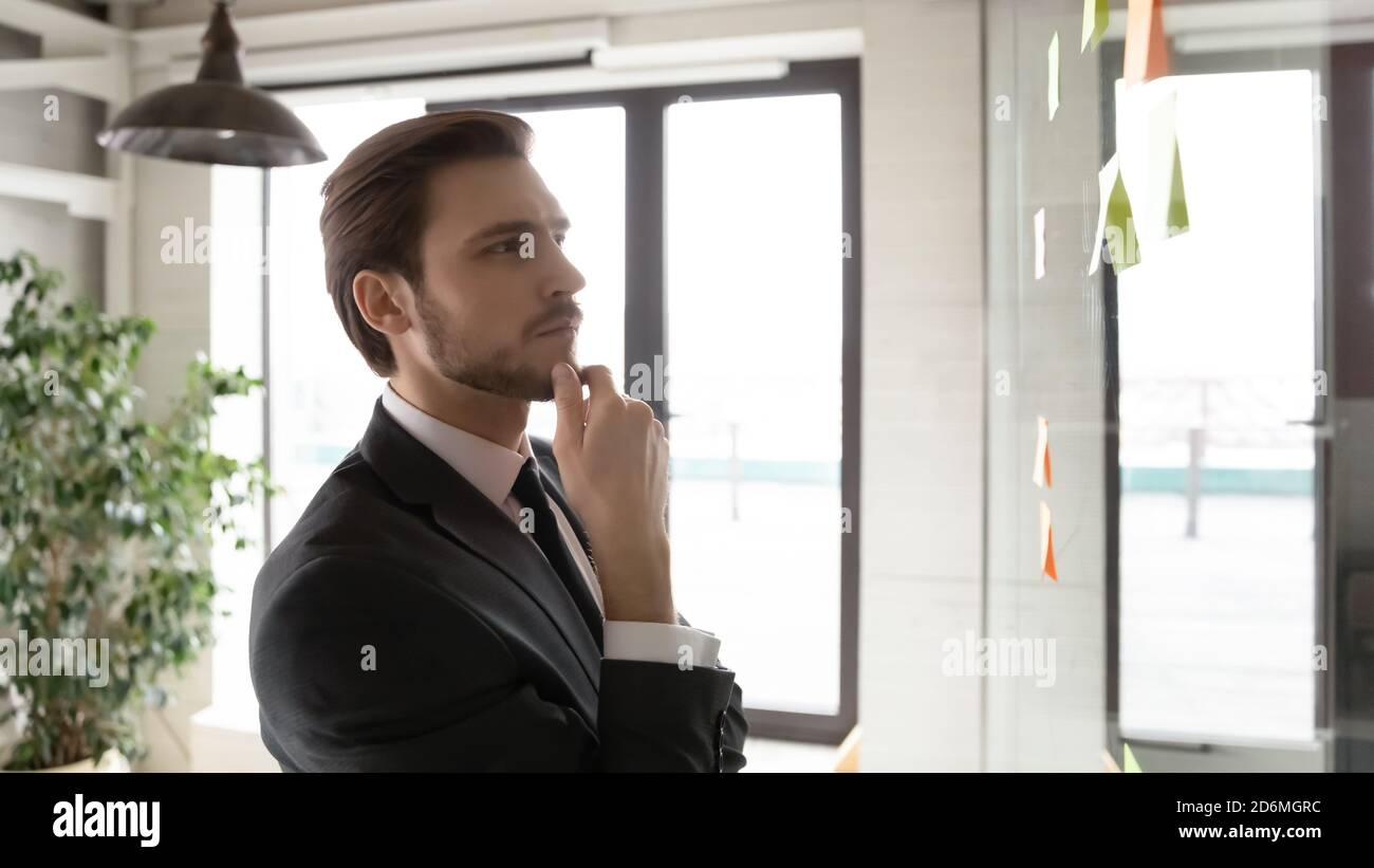 Pensive young corporate employee using project management tool. Stock Photo