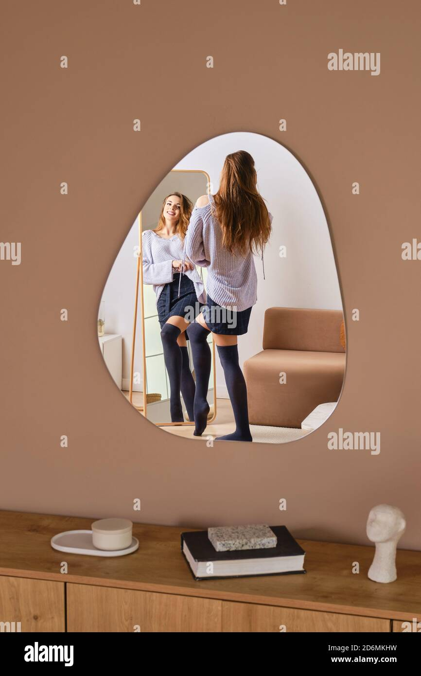 Beautiful young woman comes to the mirror, looks at herself and fix clothes Stock Photo