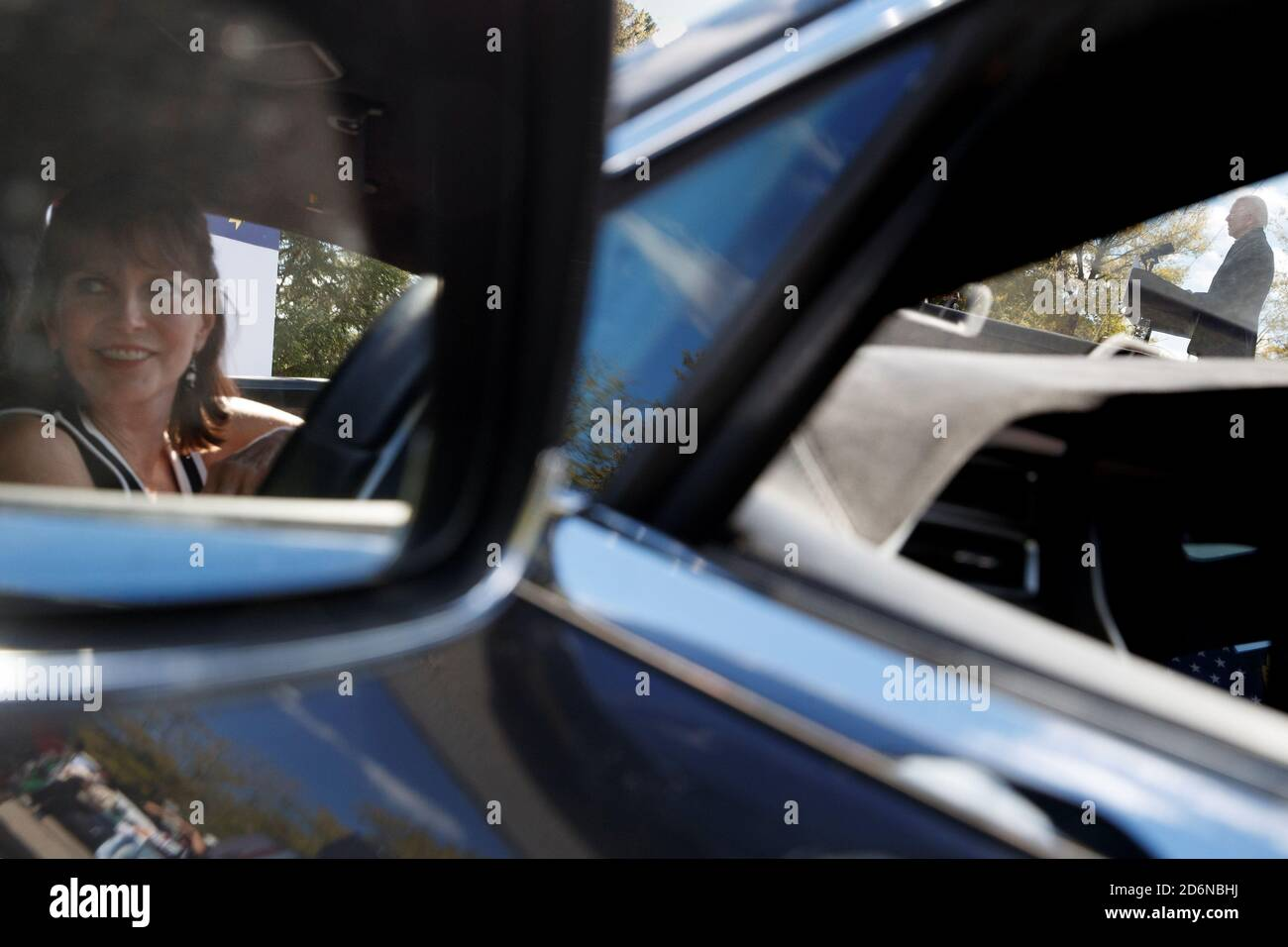 Alisa Edwards Smith, of Chapel Hill, NC, looks on from her vehicle as U.S. Democratic presidential candidate Joe Biden delivers remarks at a voter mobilization event at Riverside High School in Durham, North Carolina, U.S., October 18, 2020.  REUTERS/Tom Brenner Stock Photo