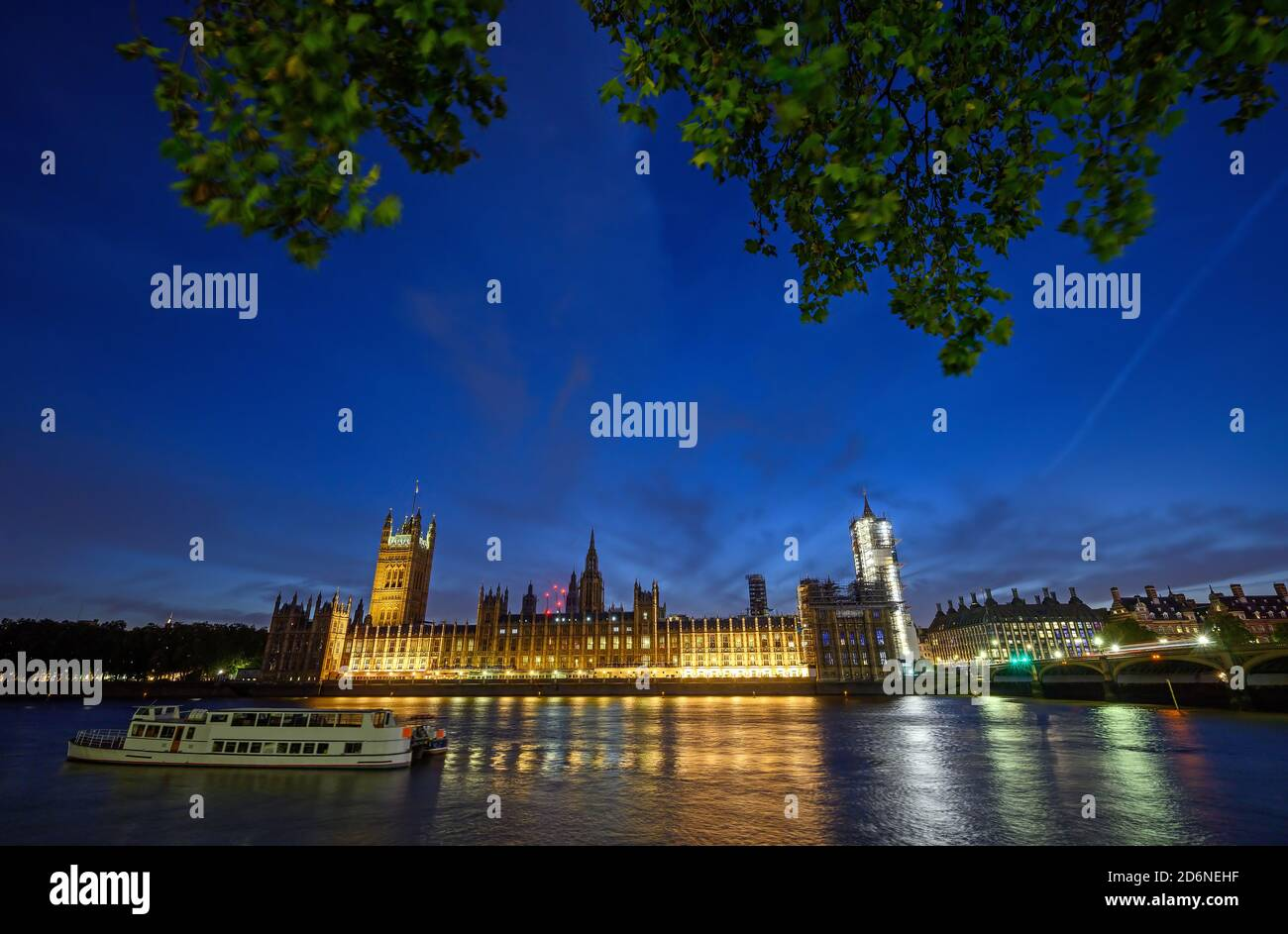 Houses of Parliament in Westminster, London, UK. View across the Thames with Westminster Bridge. Boat in foreground and long exposure motion blur. Stock Photo