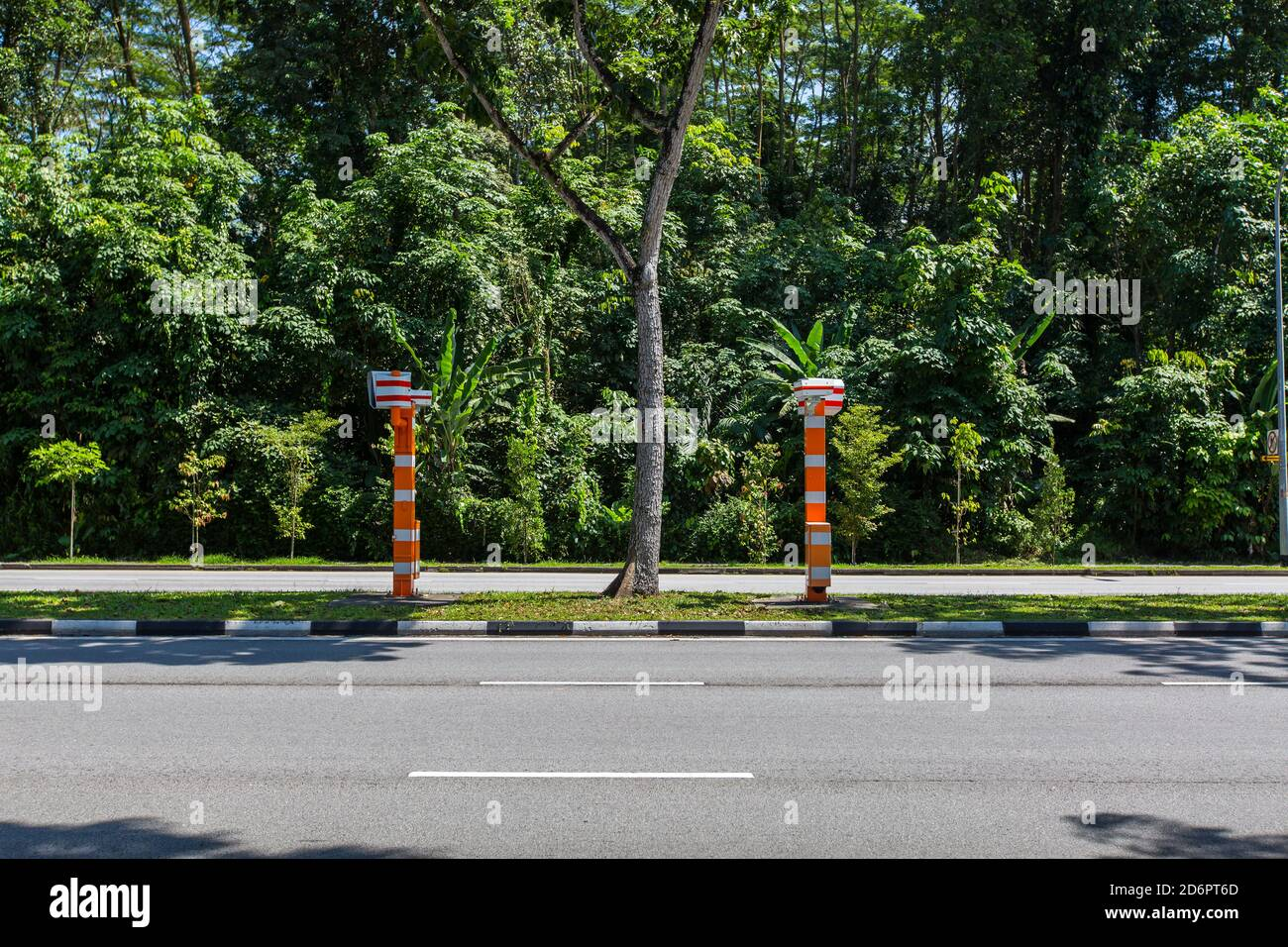 Orange and white colour police fixed speed camera (FSC) fixed on the divider of the road to discourage drivers from speeding up from afar. Stock Photo