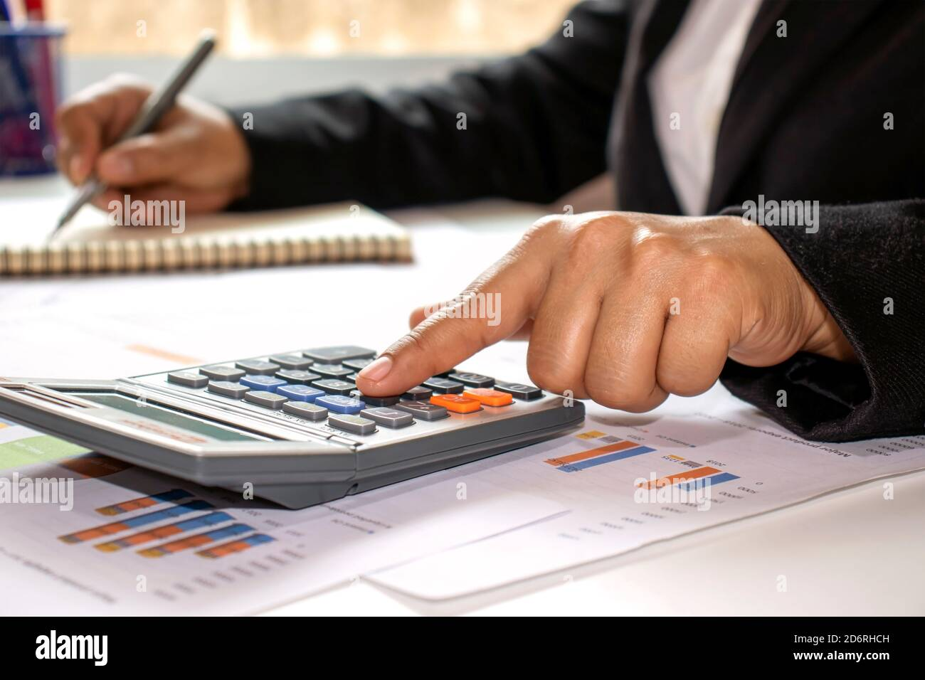 Close-up of women using calculators to create accounting reports by the window in their own homes, cost calculation concepts, and work at home concept Stock Photo