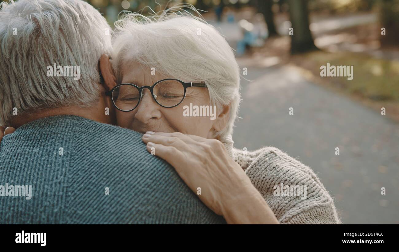 Happy old enjoying day in park. Senior man flirting with elderly woman. Dance in autumn day. High quality photo Stock Photo