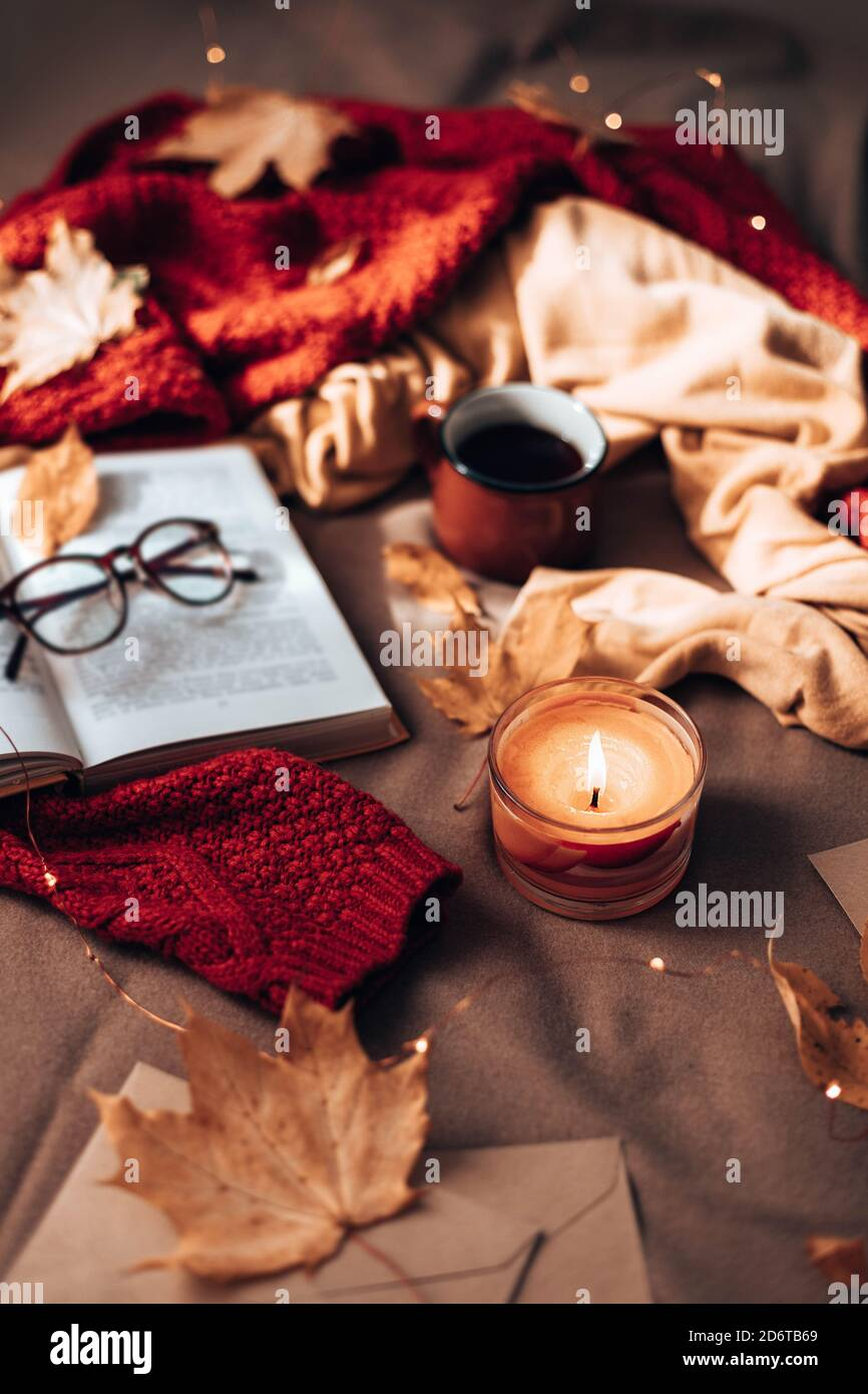 Burning candles, cup of hot tea, open book and glasses on plaid in bed. Autumn leaves and light garland decor on sofa. Autumn style. Hygge concept, vertical photo orientation Stock Photo