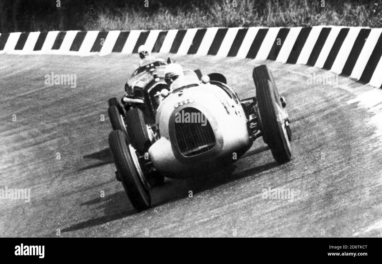 The driver Tazio Nuvolari on an Alfa Romeo is tailing a competitor on the Auto Union, Monza Grand Prix, 1930s. --- Il pilota Tazio Nuvolari su Alfa Romeo tallona un concorrente su Auto Union, Gran Premio di Monza, Anni 30. Stock Photo