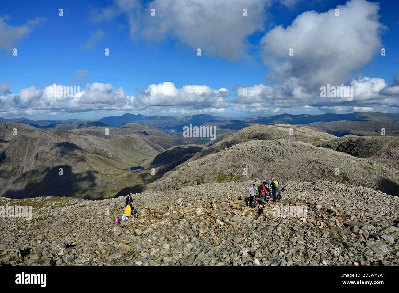 The summit plateau of Scafell Pike in Lake District National Park. Hikers take a break on the peak and take in the view stretching to Derwent Water. Stock Photo