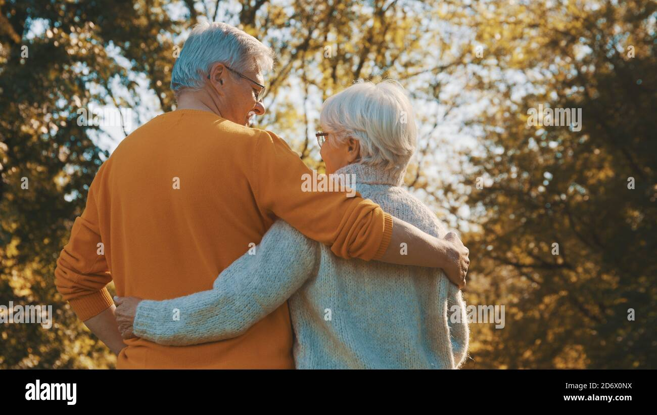 Happy old couple hugging in park. Senior man flirting with elderly woman. Romance at old age on autumn day. High quality photo Stock Photo