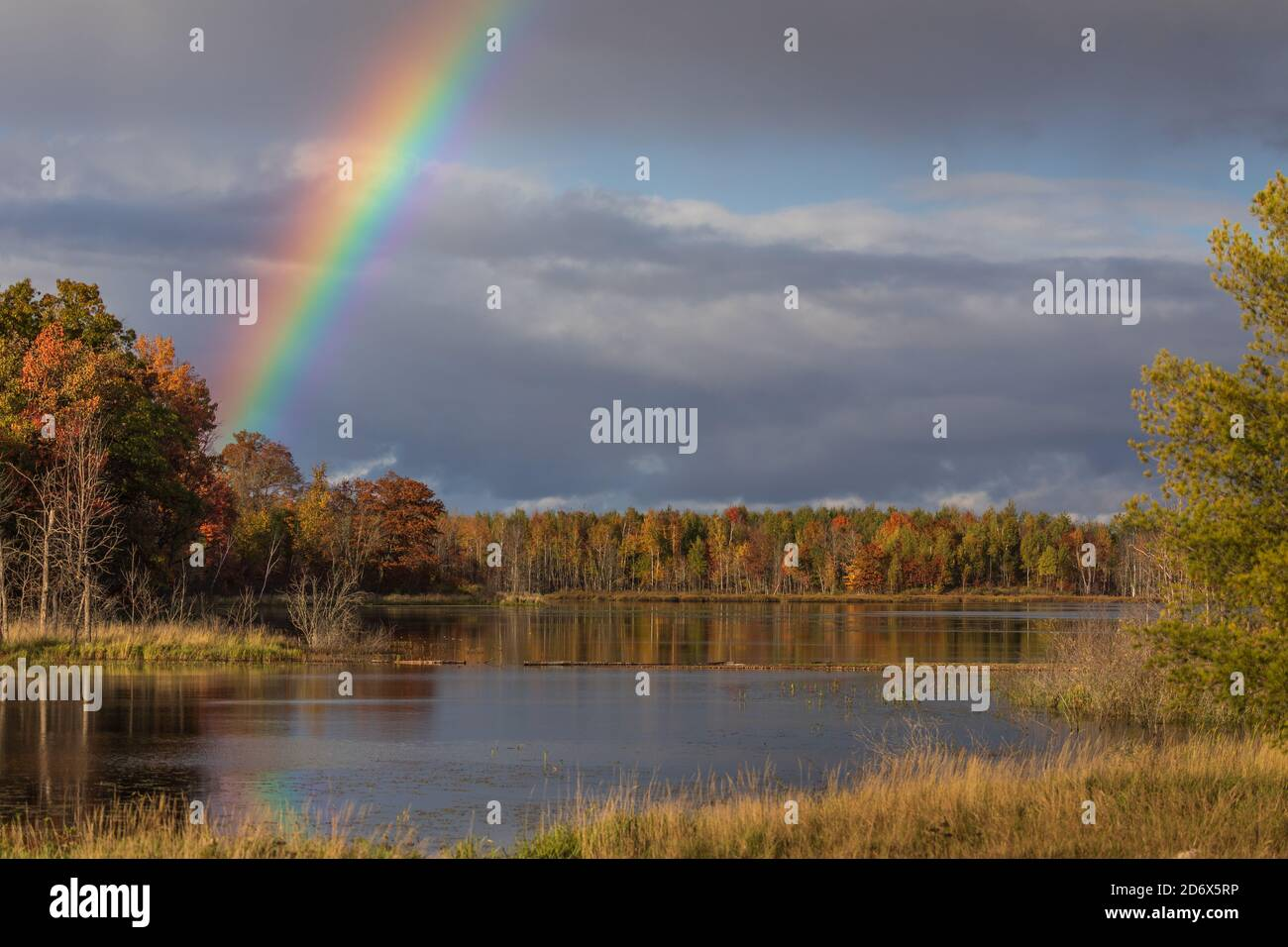 A pretty rainbow over a wilderness lake in northern Wisconsin. Stock Photo