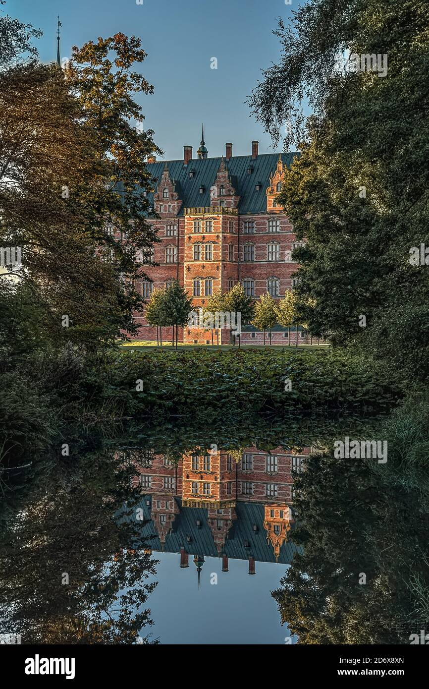 Royal Frederiksborg castle in the woods is reflected in a mirror-shiny pond, Hillerod, Denmark, October 17, 2020 Stock Photo