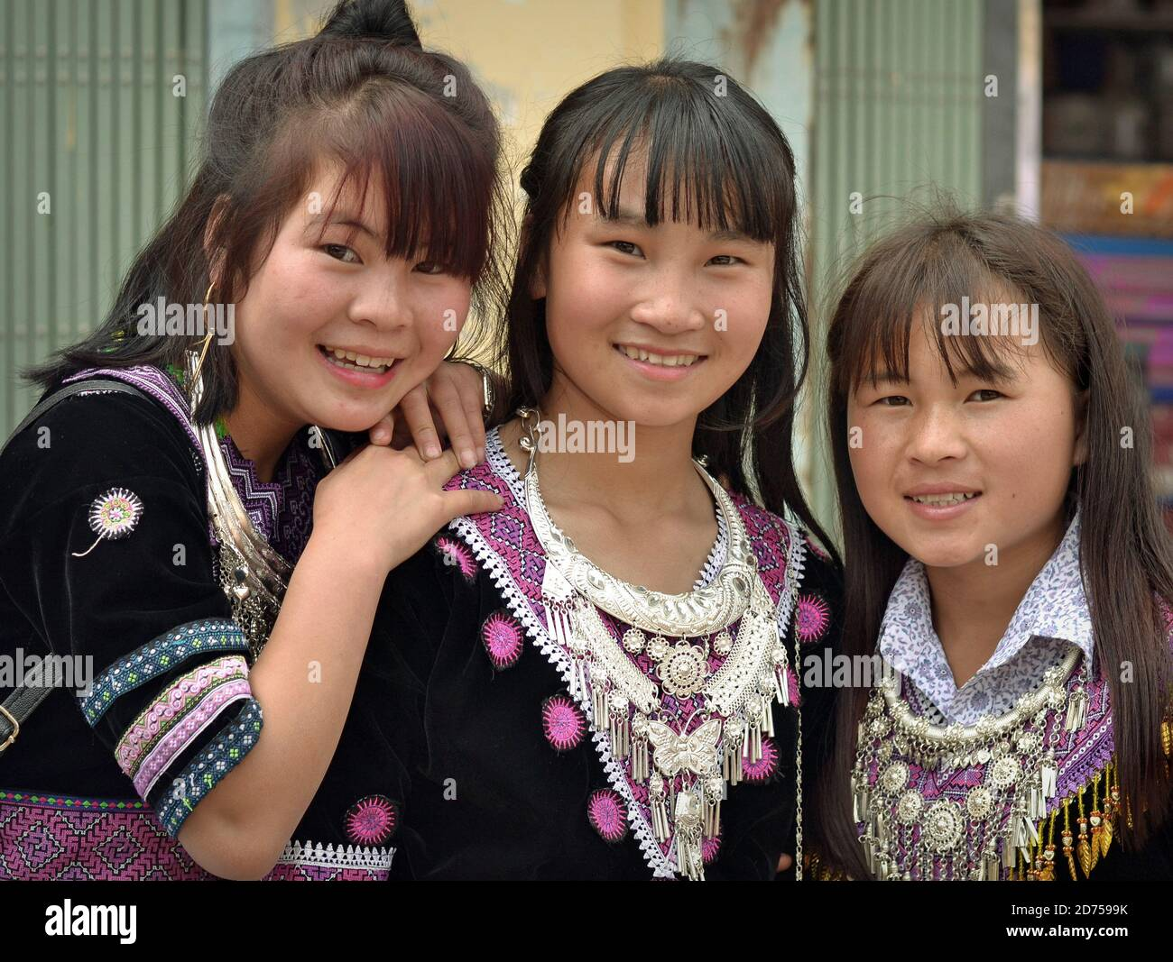 Three Vietnamese Hmong teenage girls wear their clan's traditional embroidered Sunday Best with heavy silver necklaces and smile for the camera. Stock Photo