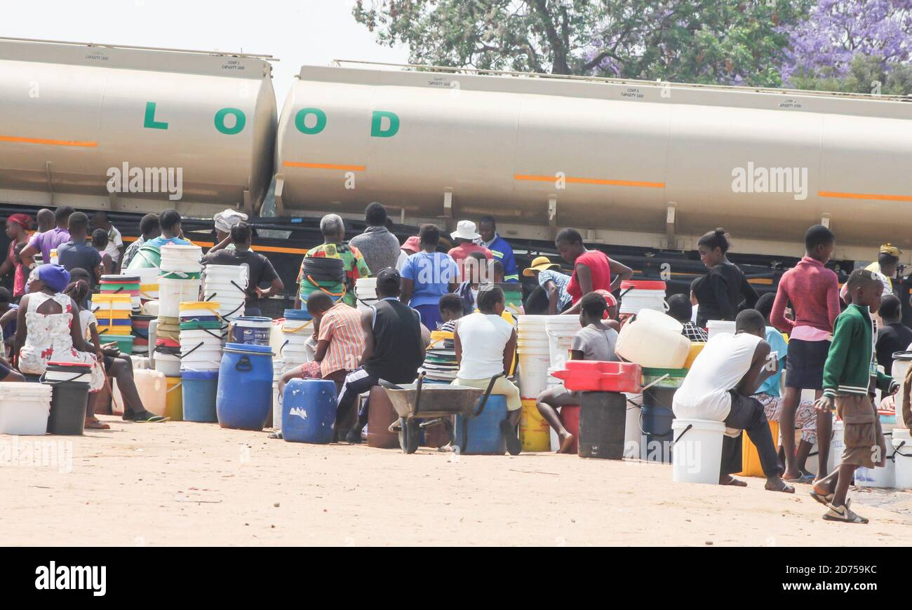 Residents in Chitungwiza gather to receive free water from the local mucipality. Chitungwiza residents have not had water for the last 10 years and only rely on borehole and other various sources of water. Zimbabwe. Stock Photo