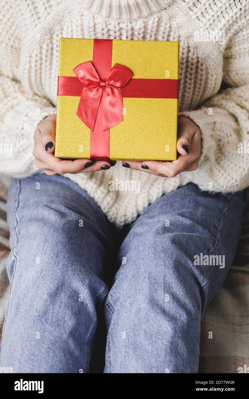 Young woman sits on bed in cozy knitted wool white sweater and holding gift-box with red gold. Hygge, New Years, Christmas, holiday preparations. Cand Stock Photo