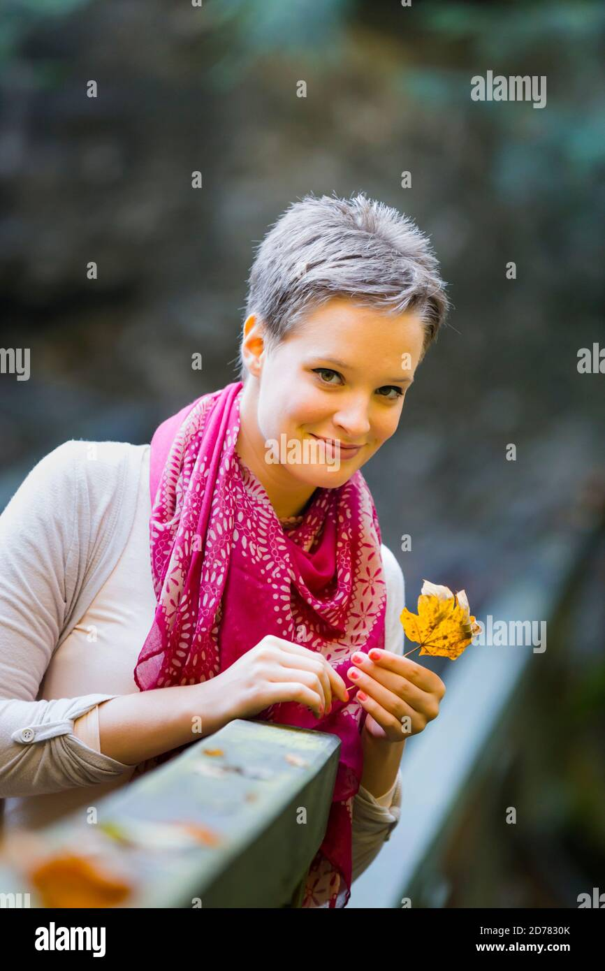 Charming charismatic photogenic appealing Portrait isolated hand hold holding fallen leaf Fall Autumn in country-side countryside countrygirl teengirl Stock Photo