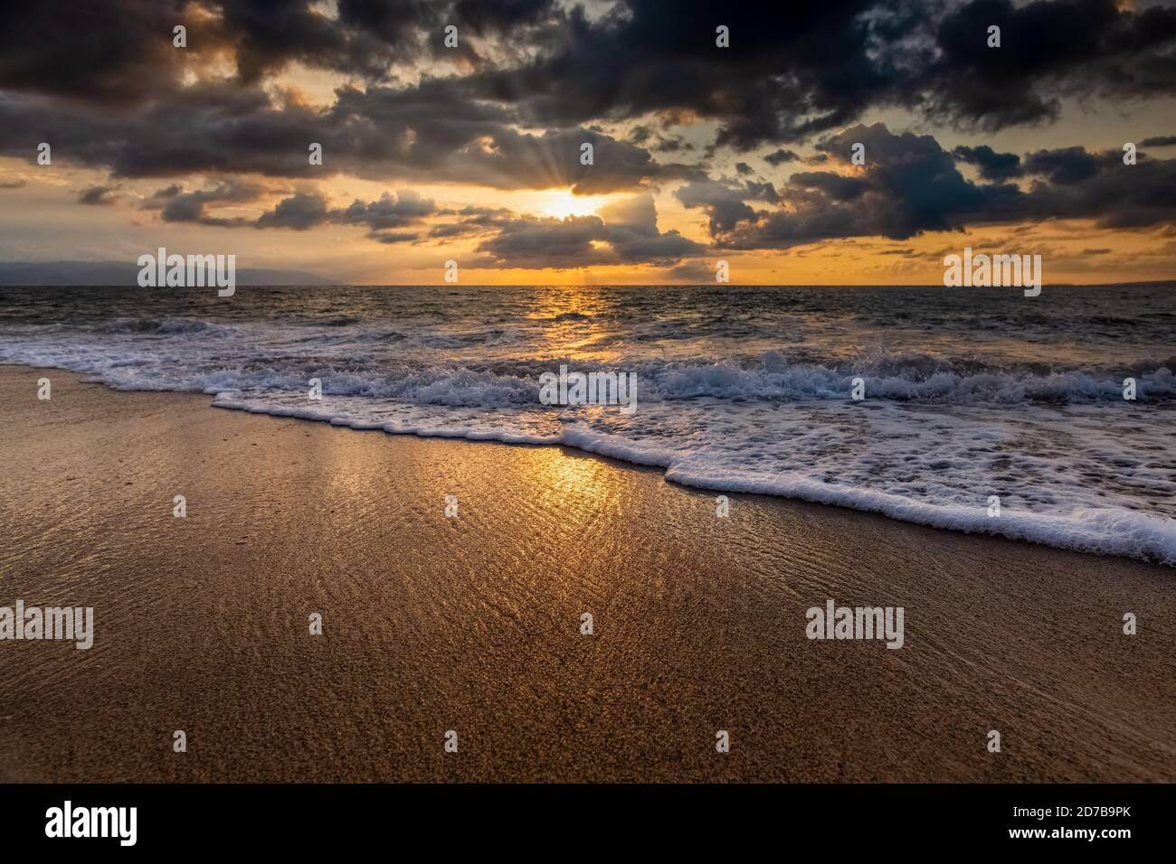 The Sun is Setting on the Ocean Horizon as Sun Rays Burst Through The Clouds Stock Photo
