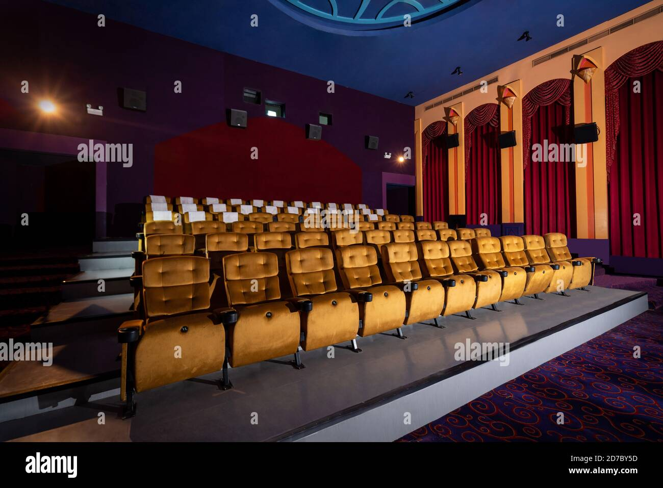 Large cinema theater interior with seat rows for audience to sit in movie theater premiere by cinematograph projector. The cinema theater is decorated Stock Photo