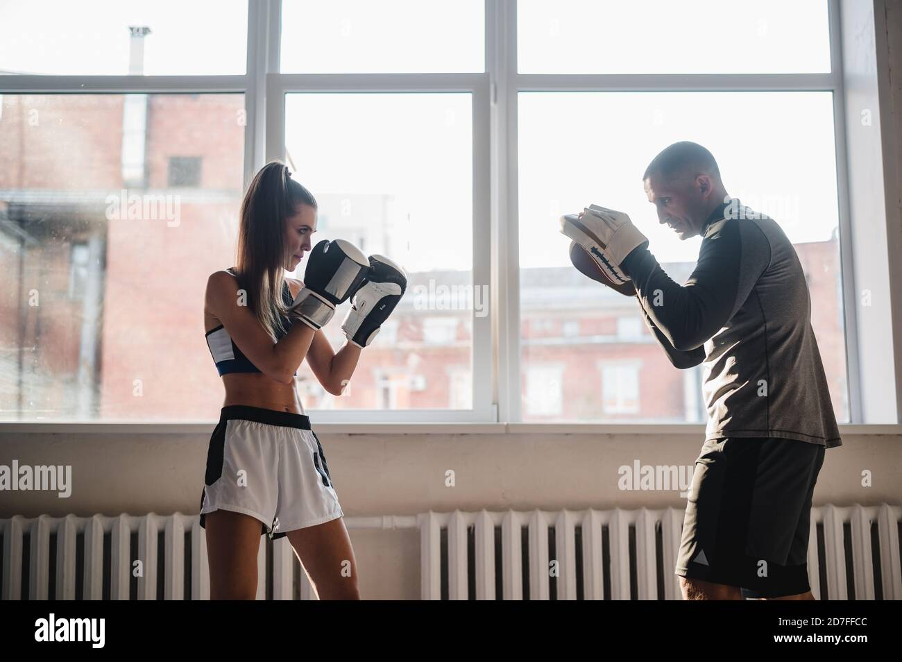A man with boxing paws on his hands teaches the technique of hitting a novice girl in a light gym Stock Photo