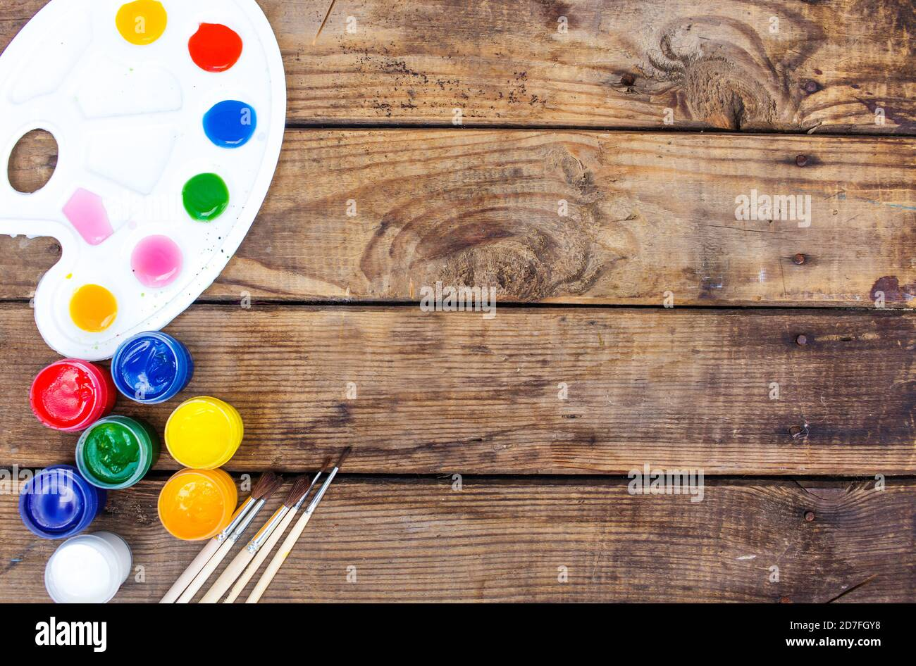 multi-colored paints,brushes palette, brush,lie on a wooden background top view Stock Photo