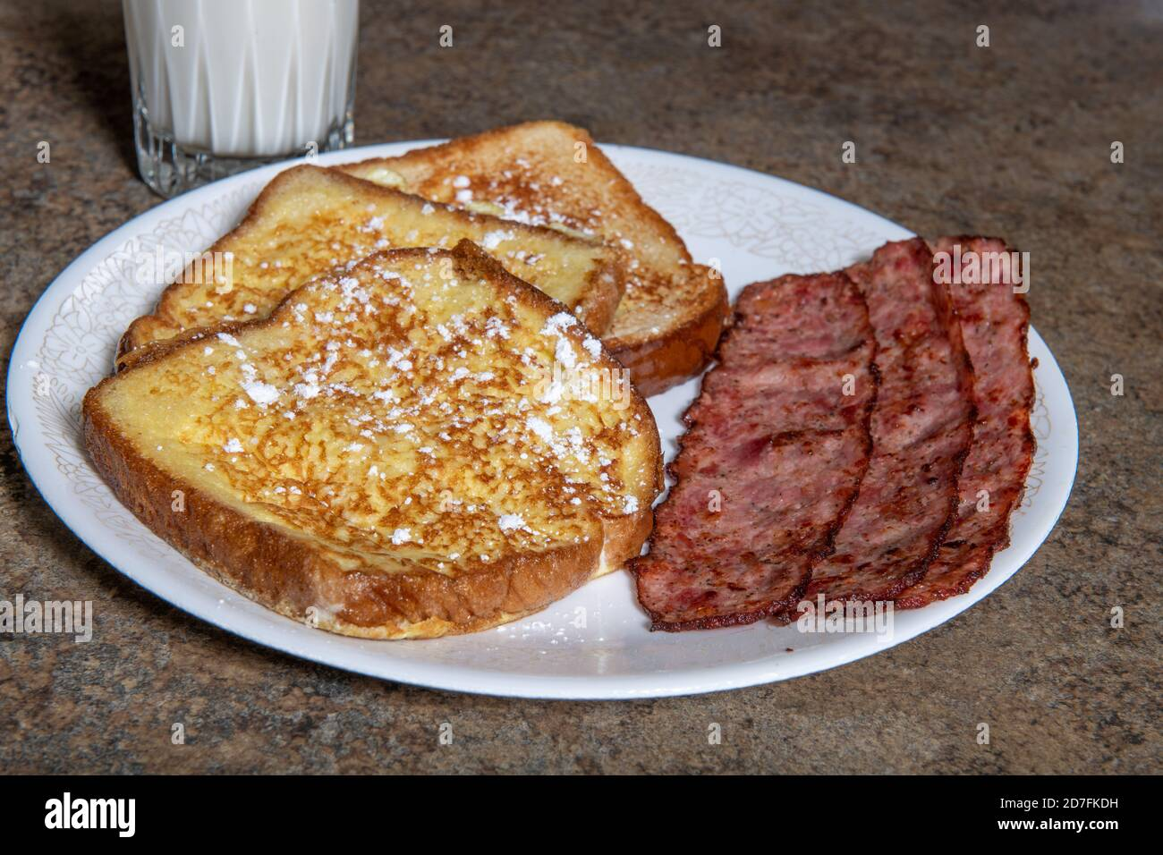 A plate of French toast that has powdered sugar and bacon Stock Photo