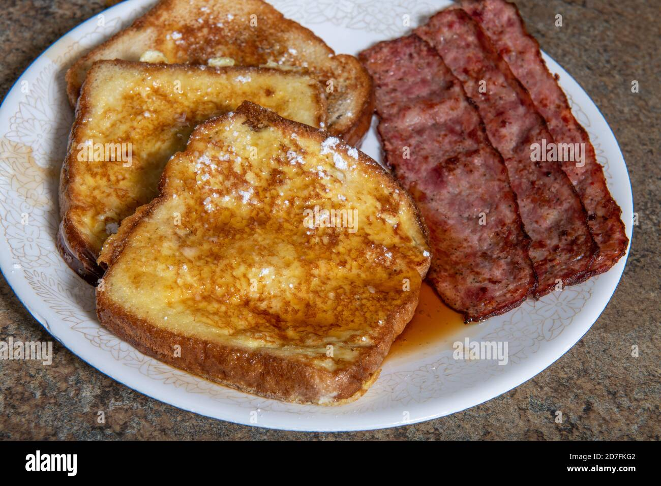 A plate of French toast that has powdered sugar and maple syrup on it with bacon Stock Photo