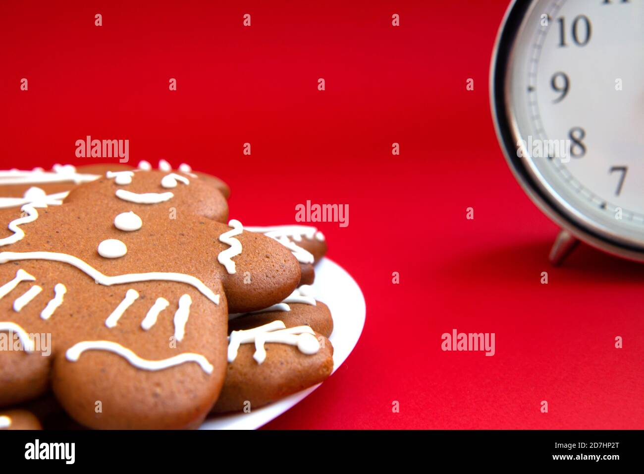 Beautiful vintage silver alarm clock and in the foreground plate of gingerbread cookies on a bright red background. Time concept. Holiday routine. Wai Stock Photo