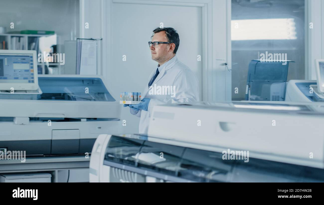Male Research Scientist Walks Through Laboratory with Tray of Test Tubes Filled with Samples. In the Background Working Laboratory with Innovative Stock Photo