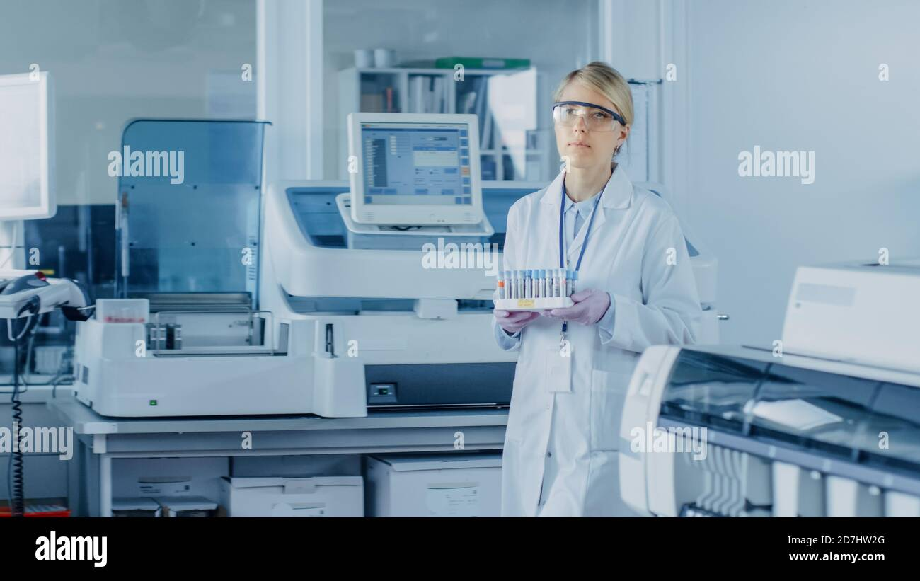 Female Research Scientist Walks Through Laboratory with Tray of Test Tubes Filled with Samples. In the Background People Working in Laboratory with Stock Photo