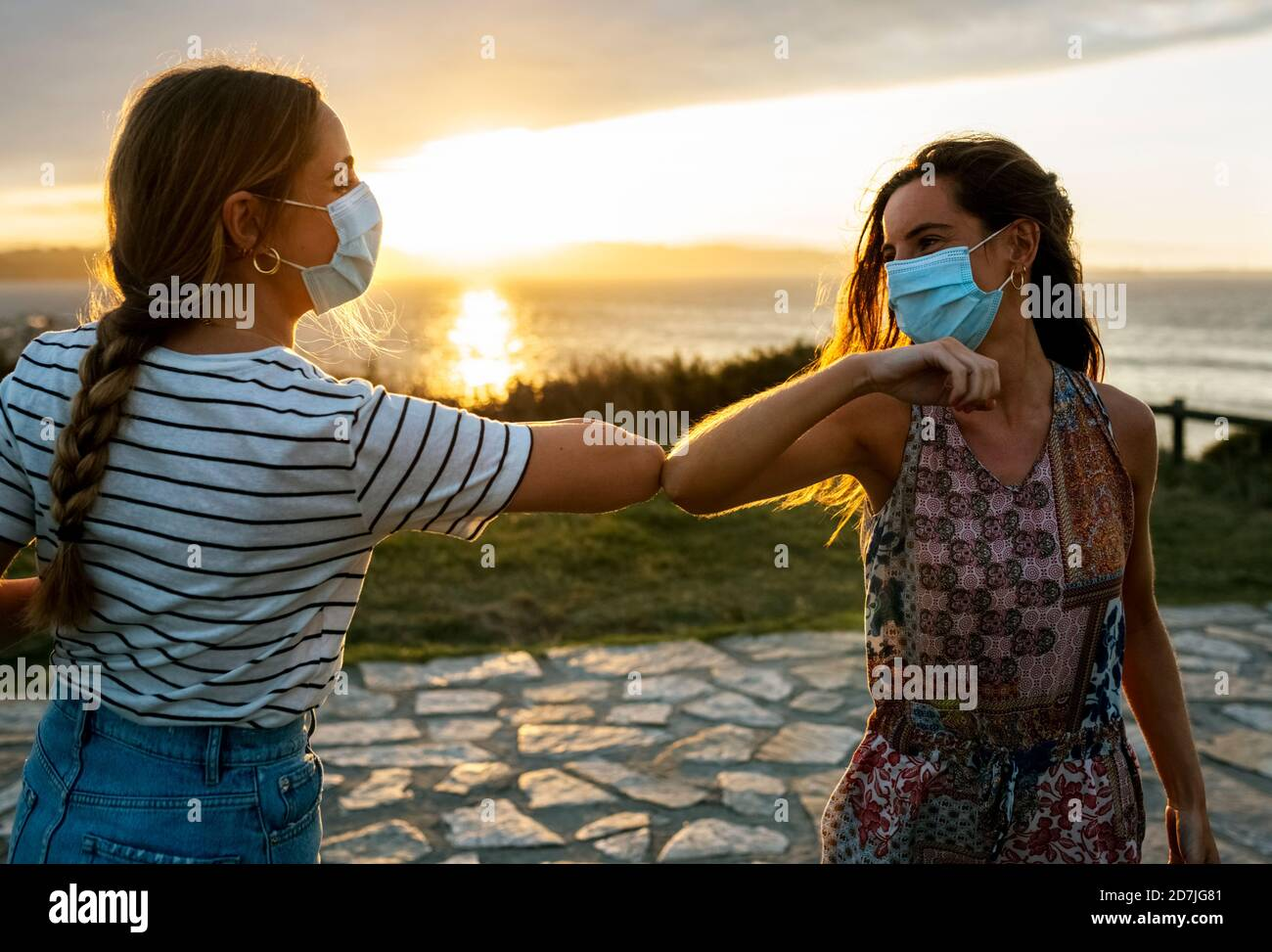 Women in protective face masks elbow bumping against sky during COVID-19 outbreak Stock Photo