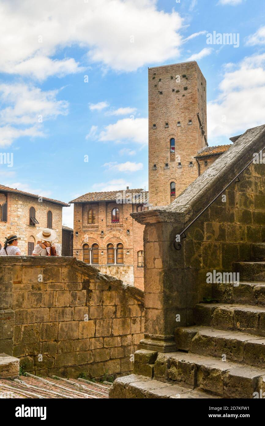 Tourist women with hats on the stairs of the Duomo of San Gimignano admiring the main square with the medieval Torre Chigi, Siena, Tuscany, Italy Stock Photo