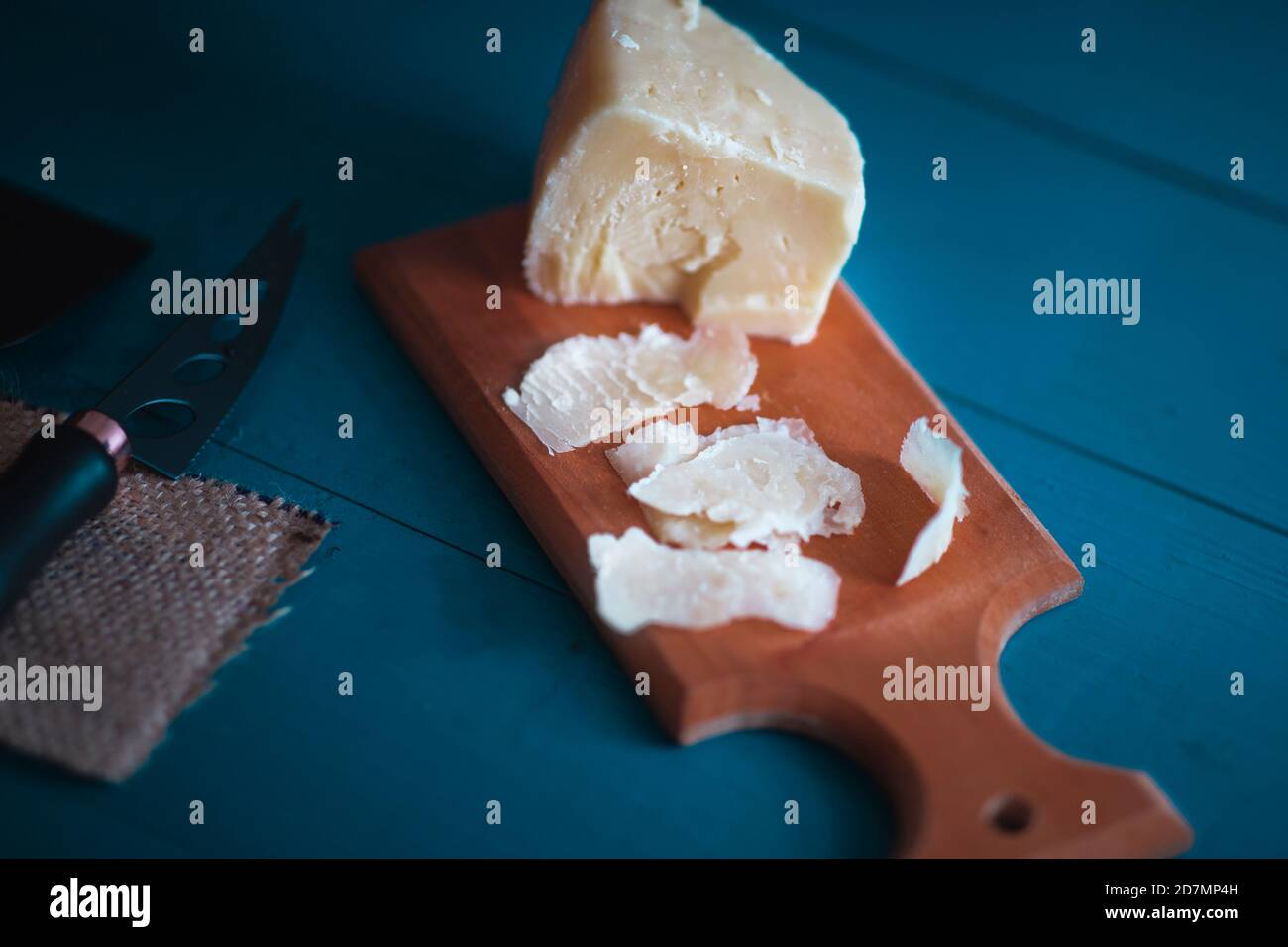 Composed cloesup detail view of aged cheddar cheese with cheese knife set, over vintage blue wooden backdrop Stock Photo