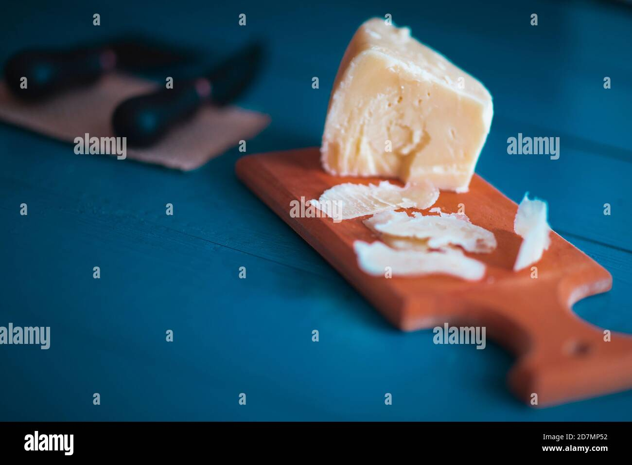 Composed cloesup detail view of aged cheddar cheese with cheese knife set, over vintage blue wooden backdrop, copy space includes Stock Photo