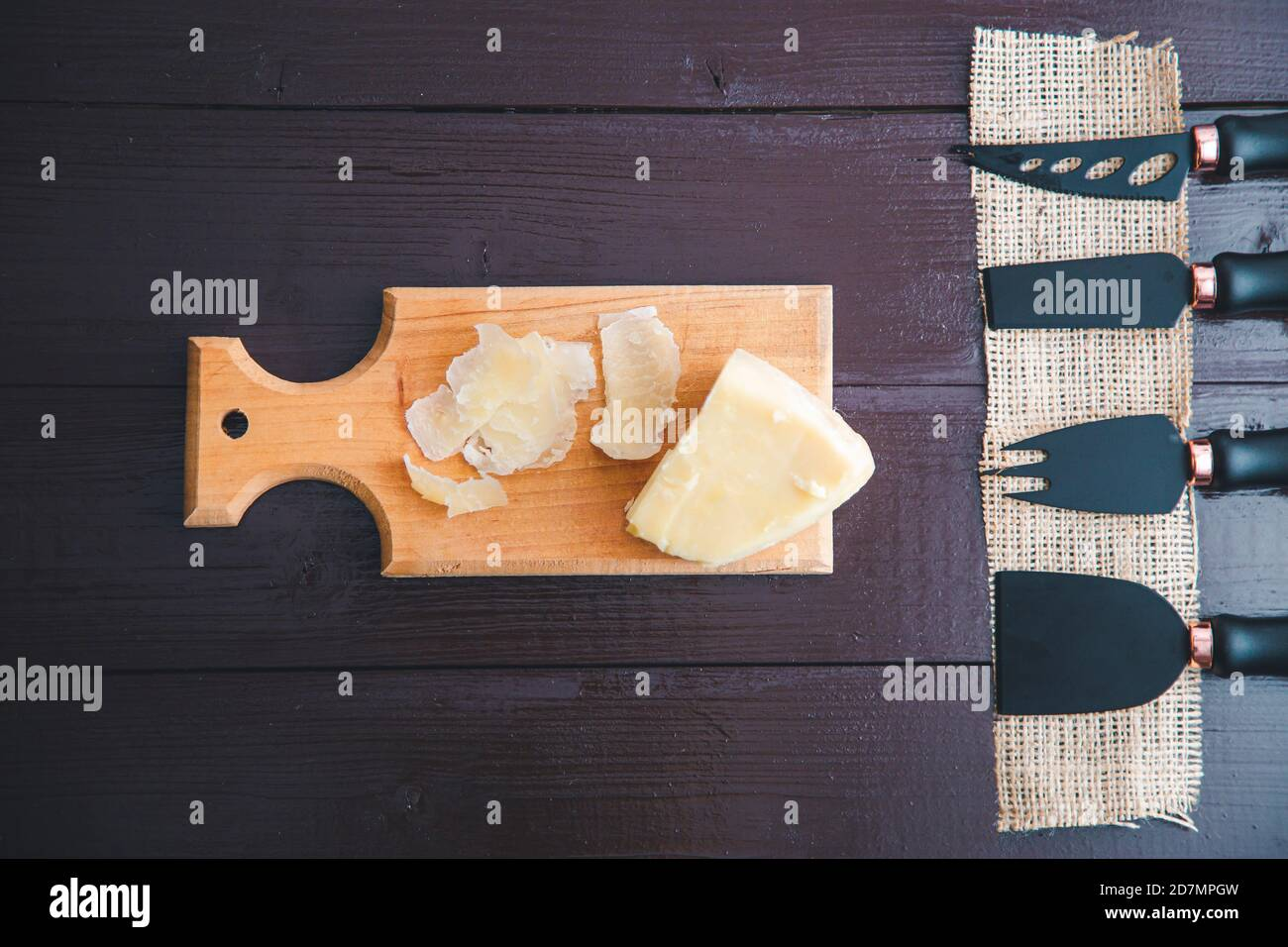 Composed Flat lay detail view of aged cheddar cheese with cheese knife set, over vintage brown wooden backdrop with copy space Stock Photo