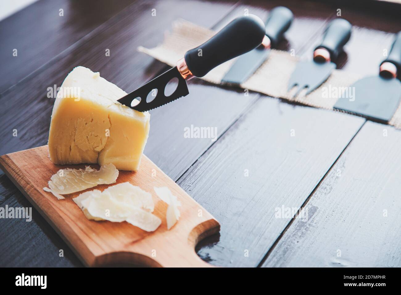 Composed cloesup detail view of aged cheddar cheese with cheese knife set, over vintage brown wooden backdrop Stock Photo