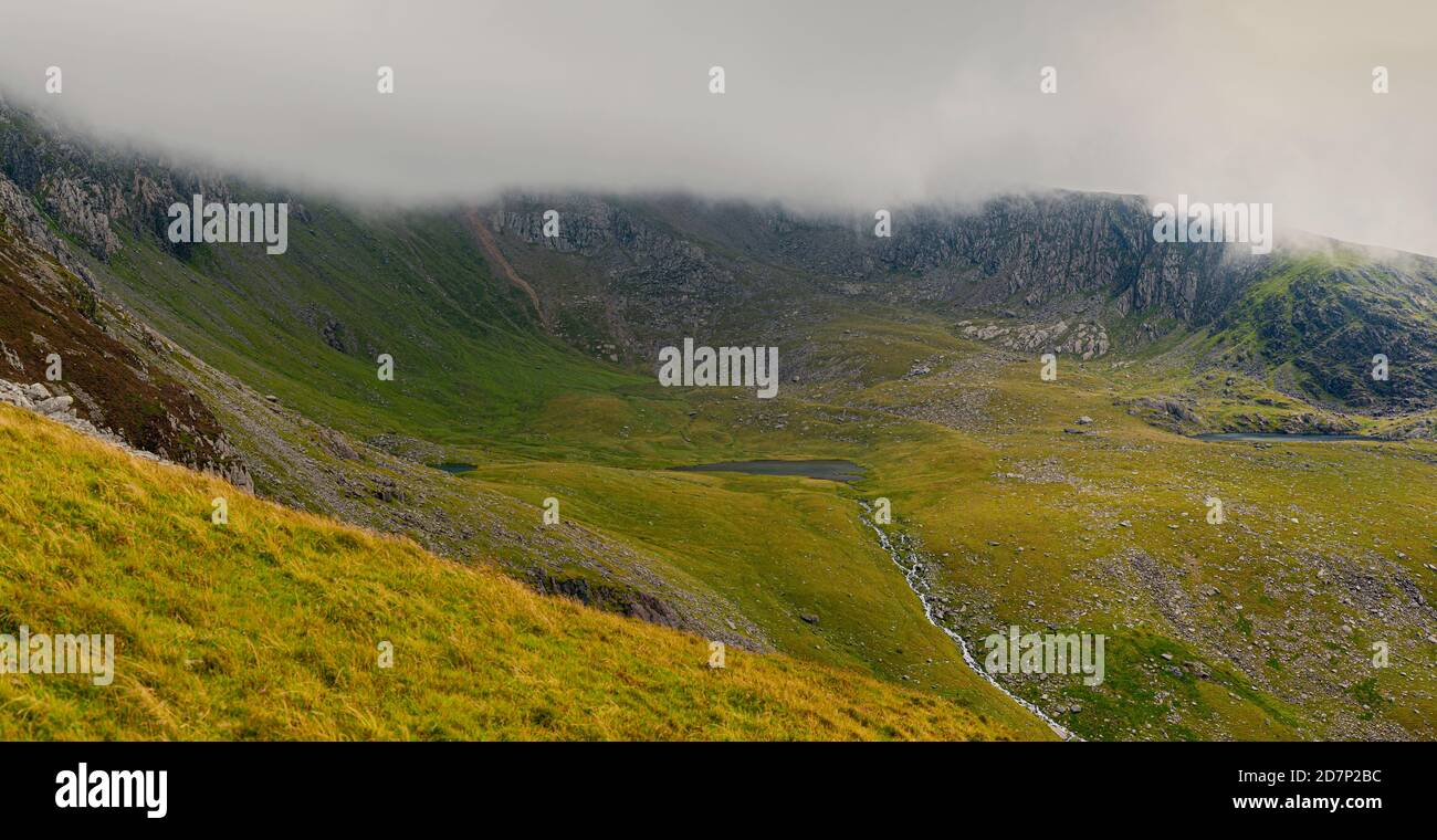 Panoramic view at Yr Wyddfa - Snowdon on cloudy day from Ranger Path. Highest mountain range in Wales covered in clouds. Snowdonia National Park. UK. Stock Photo