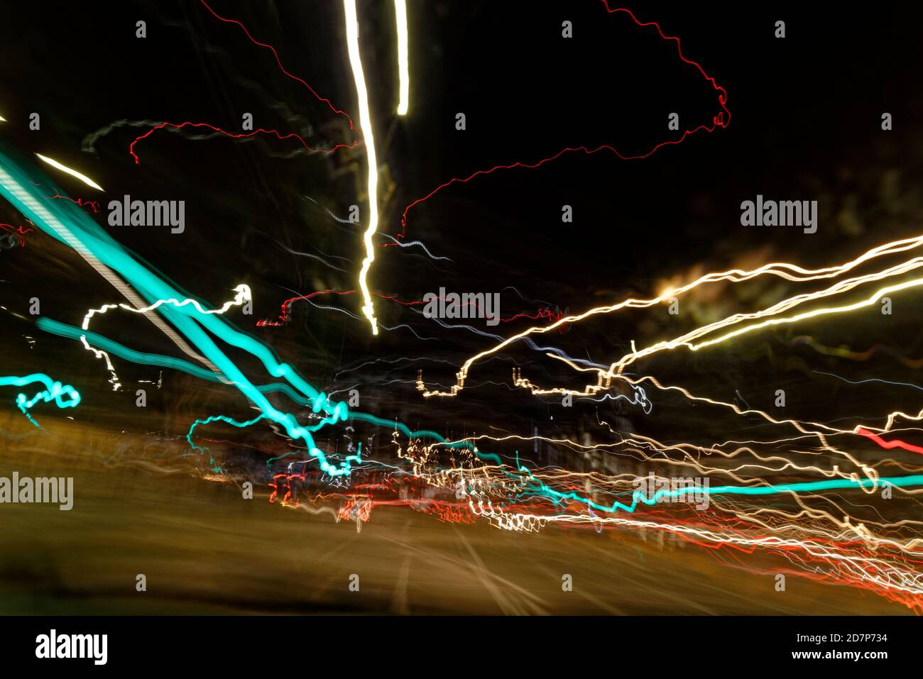 Long exposure light trails as abstract urban background. Different light trails of multicolored street lanterns and passing cars scattering in the dar Stock Photo