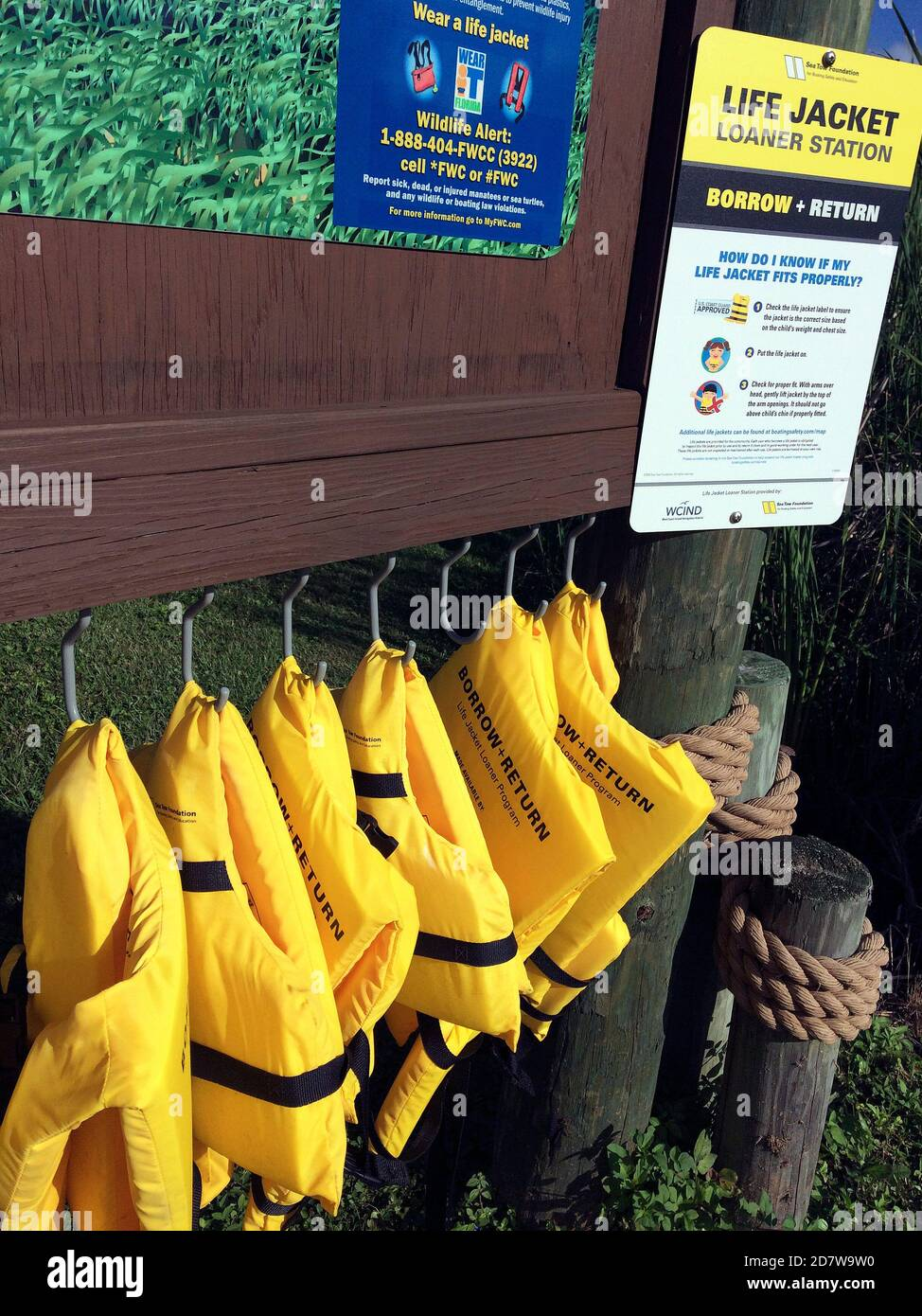 A row of bright yellow life jackets awaits boaters who have forgotten to bring a personal flotation device that helps ensure their safety at sea in the Gulf of Mexico along the west coast of Florida, USA. The buoyant vests are offered free of charge as part of a Borrow and Return program by the Sea Tow Foundation and the West Coast Inland Navigation District (WCIND). Loaner life preservers are available to prevent drownings in many places in the United States and other countries where recreation on the water is popular. Stock Photo