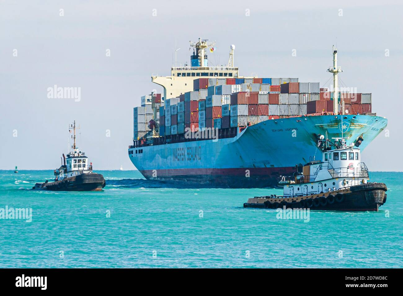 Florida Miami Beach Atlantic Ocean cargo container ship loaded, approaches approaching arrives arriving Port of Miami tugboats, Stock Photo