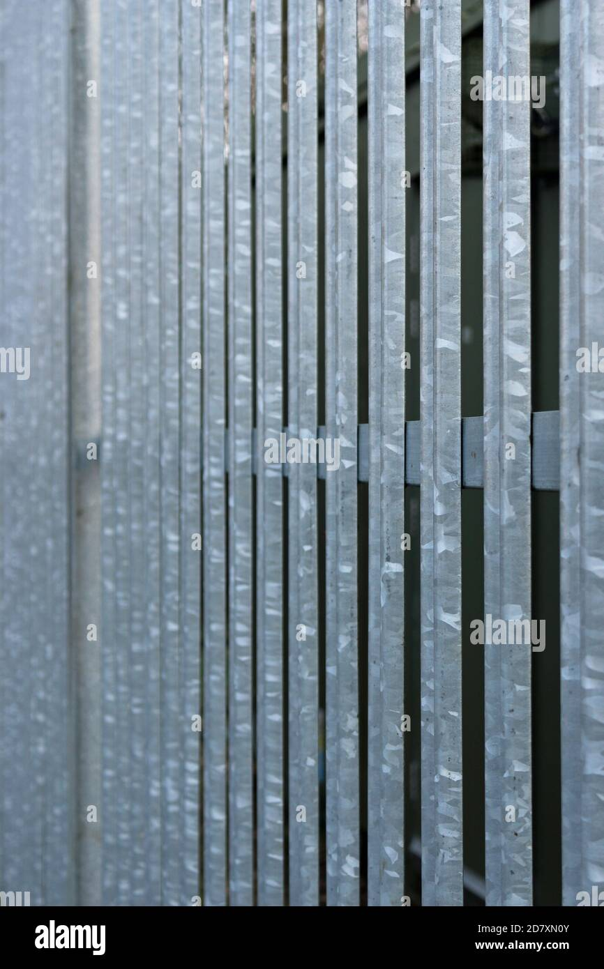 Metal palisade security fencing rails and upright pales in focus in the foreground and becoming becoming gradually more blurred into the background. Stock Photo