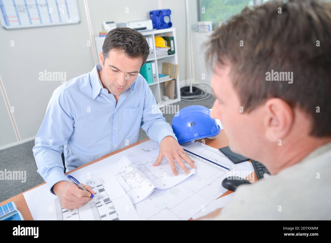Two men at desk looking at blueprints Stock Photo