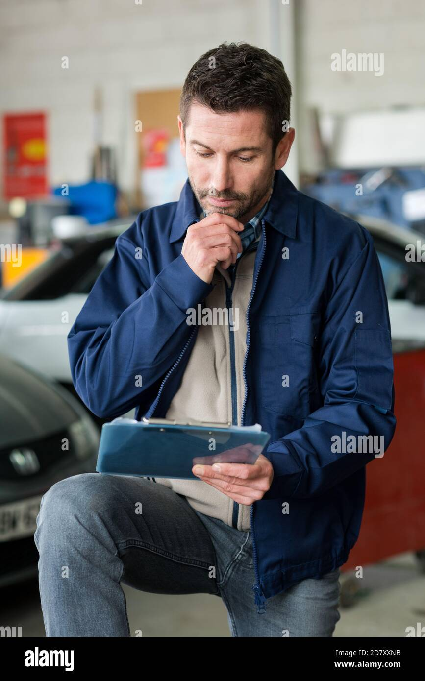 portrait of confident male mechanic with clipboard Stock Photo