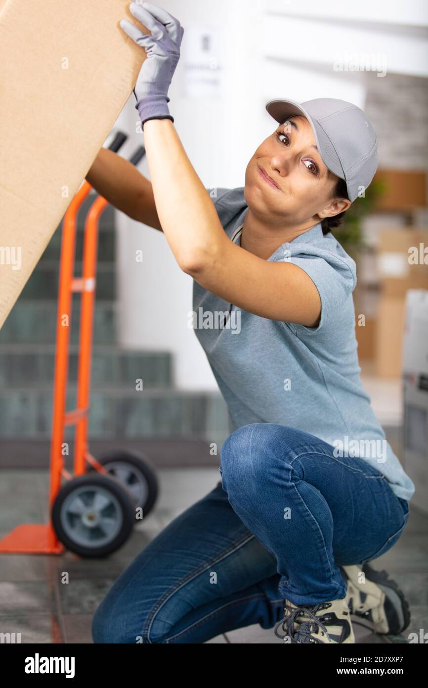 deliverywoman struggling with a pile of parcels Stock Photo