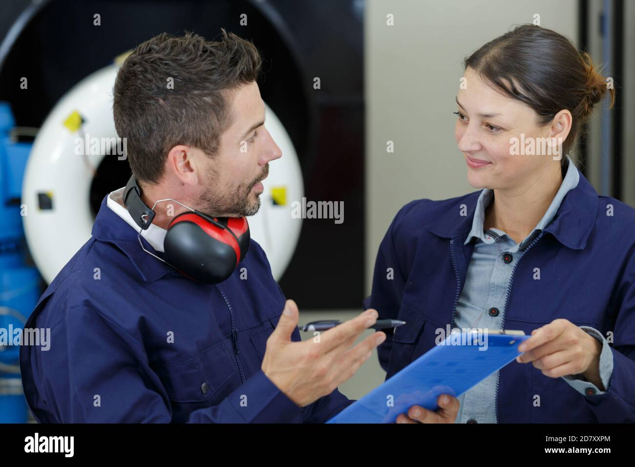 male engineers and technician talking over clipboard Stock Photo