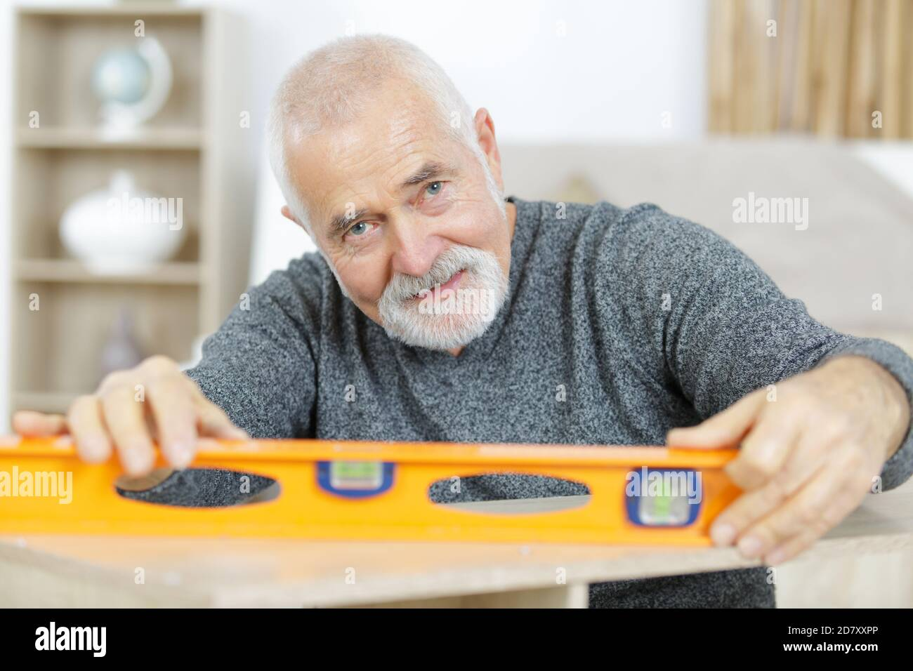 senior wood measuring with spirit level Stock Photo