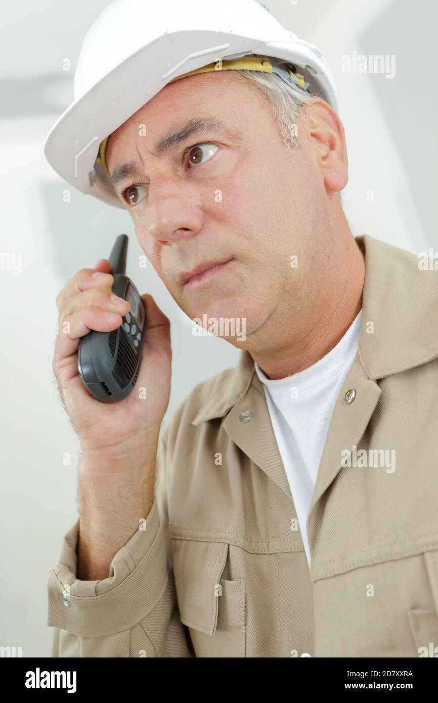 builder is talking to collegue via a walkie talkie Stock Photo