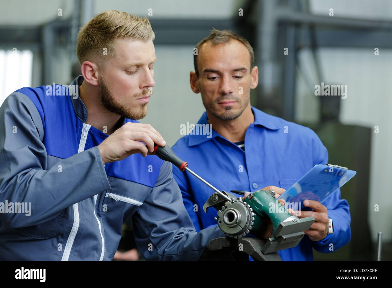 men and gear mechanism in factory Stock Photo