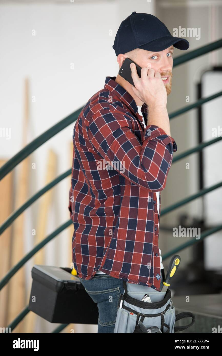 busy handyman arriving at property talking on his smartphone Stock Photo