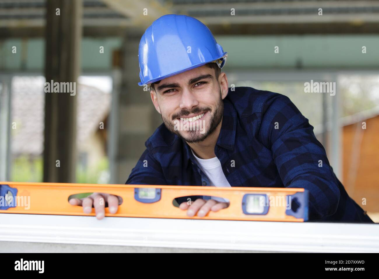 happy man is holding a building level Stock Photo