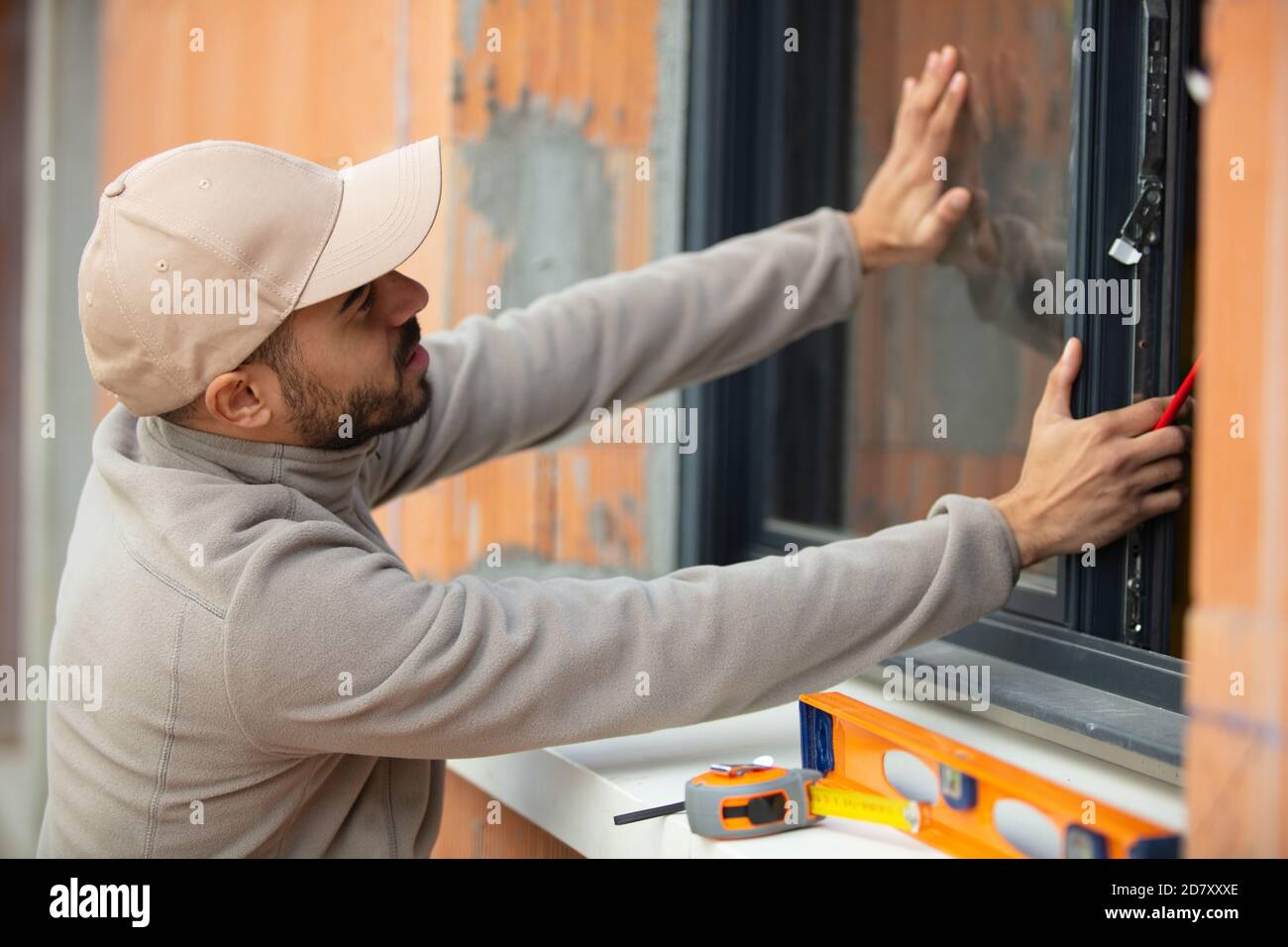 handsome young man installing bay window Stock Photo