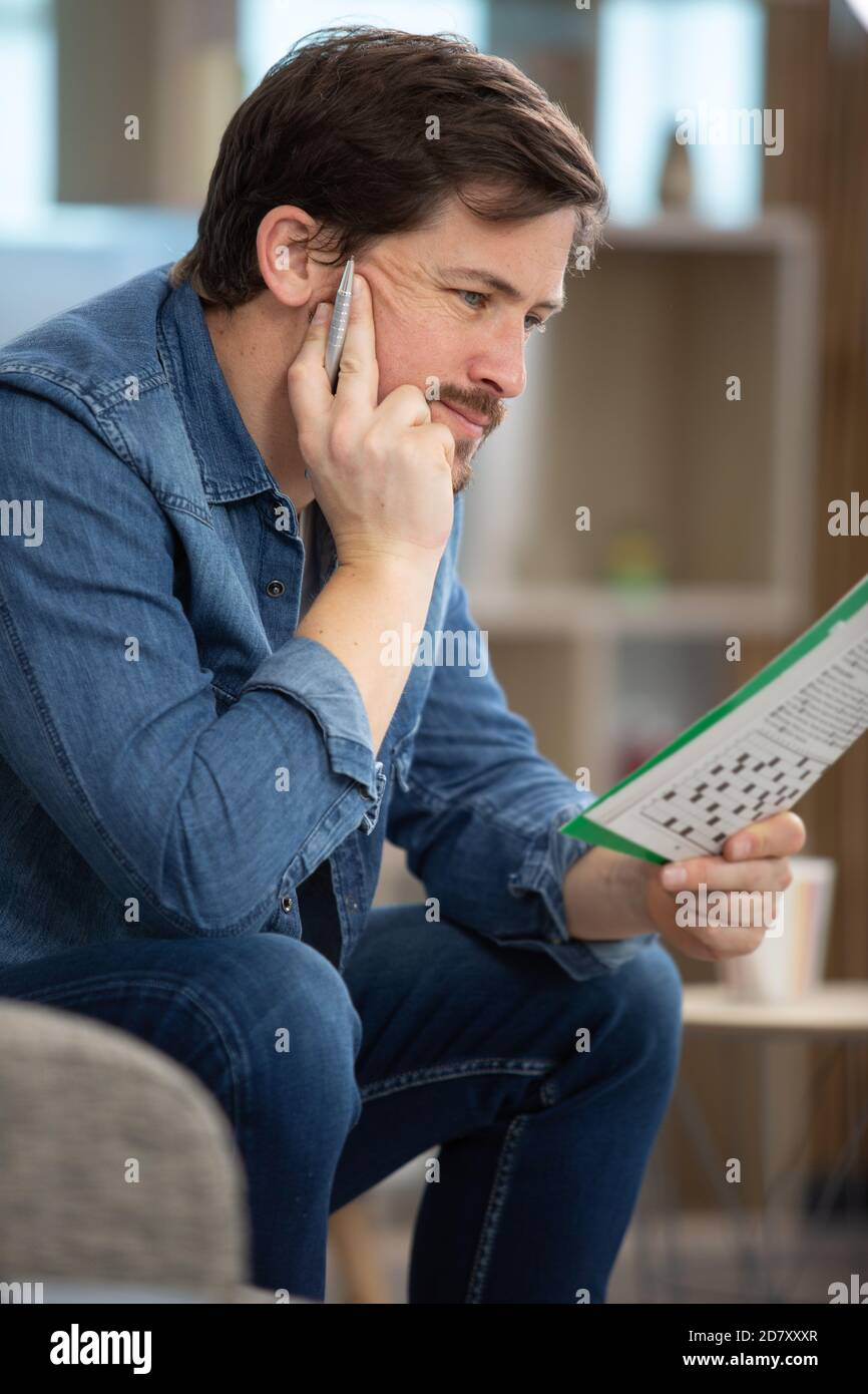 young man doing a crossword puzzle Stock Photo