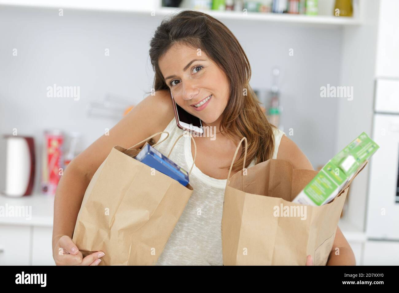 young housewife sort purchases after shopping and talking cell phone Stock Photo