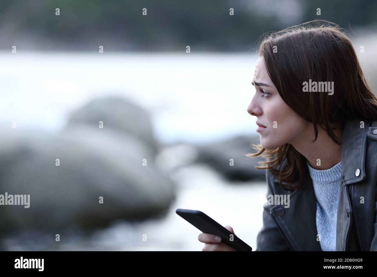 Sad woman looking away holding smart phone alone on the beach Stock Photo